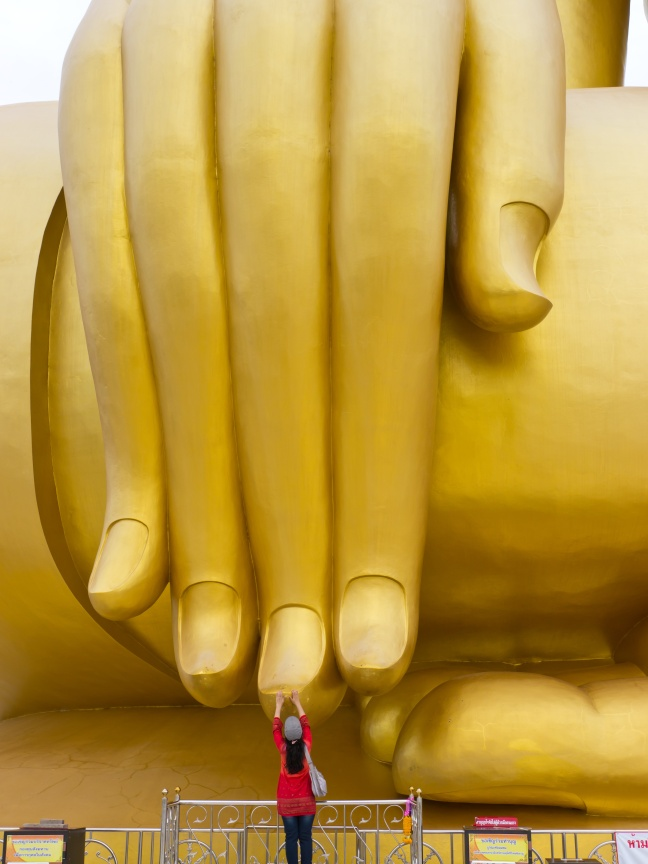 Buddhist is touching hand of big Buddha statue